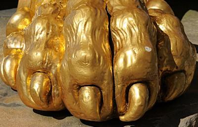 Pfote einer goldenen Löwnskulptur aus der Nähe