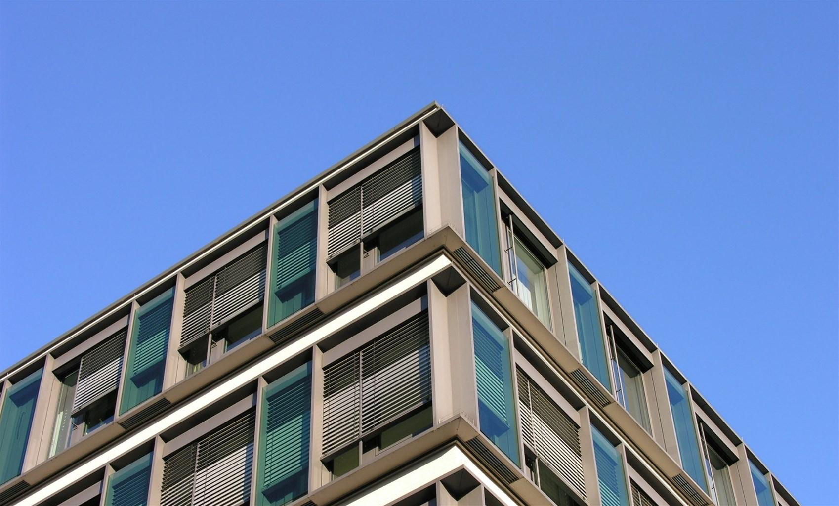 moderne, graue Hausfassade vor blauem Himmer als Hintergrund