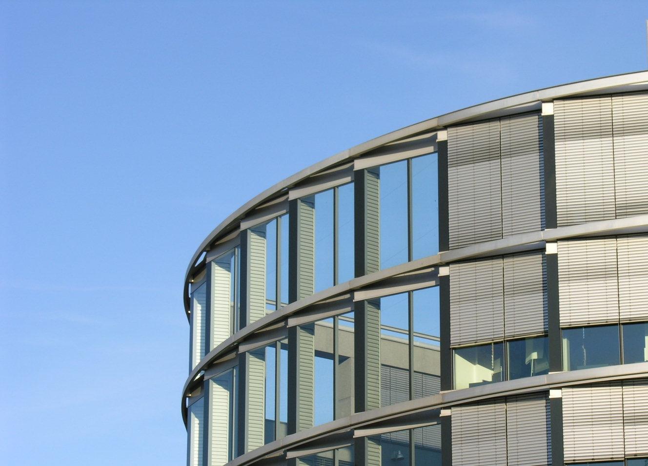 graue Stahlfassade vor blauem Himmer als Hintergrund