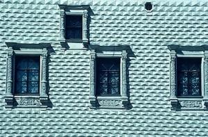 türkise Hausfassade mit vier Fenstern