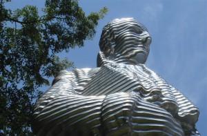 Statue aus Metall von unten vor blauem Himmel