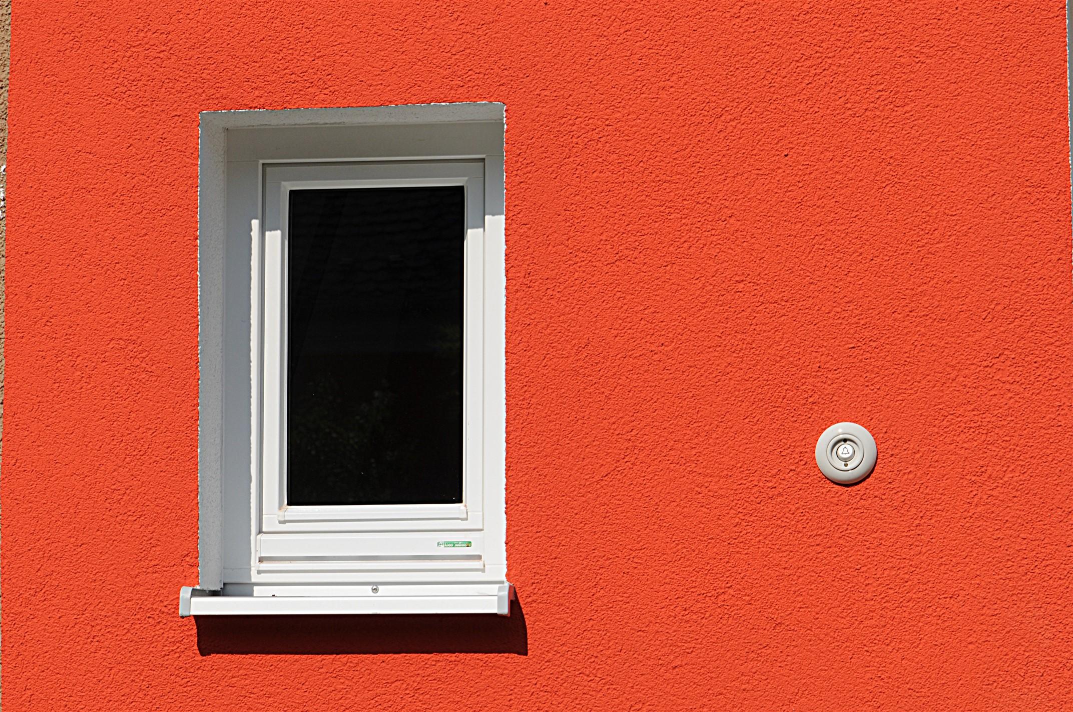Nahaufnahme rote Hausfassade mit einem Fenster und einer weißen Klingel