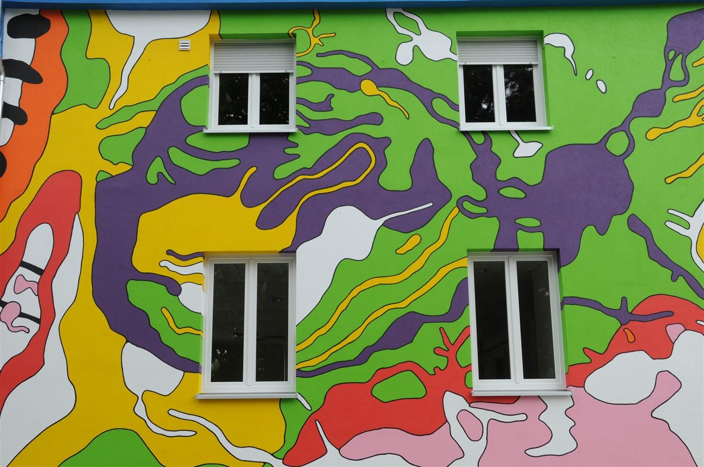 Bunte Hausfassade mit vier Fenstern