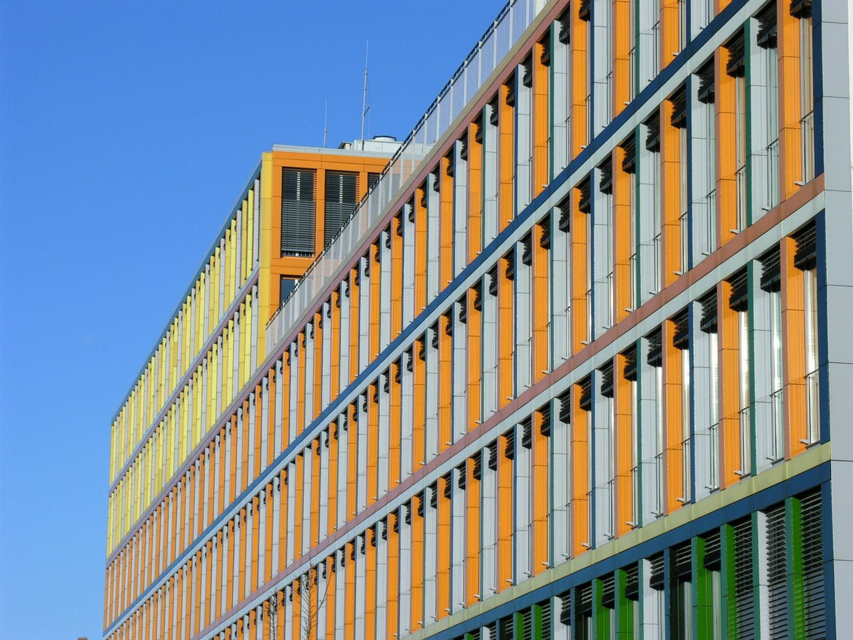 Orange-Grüne Hausfassade vor blauem Himmer als Hintergrund