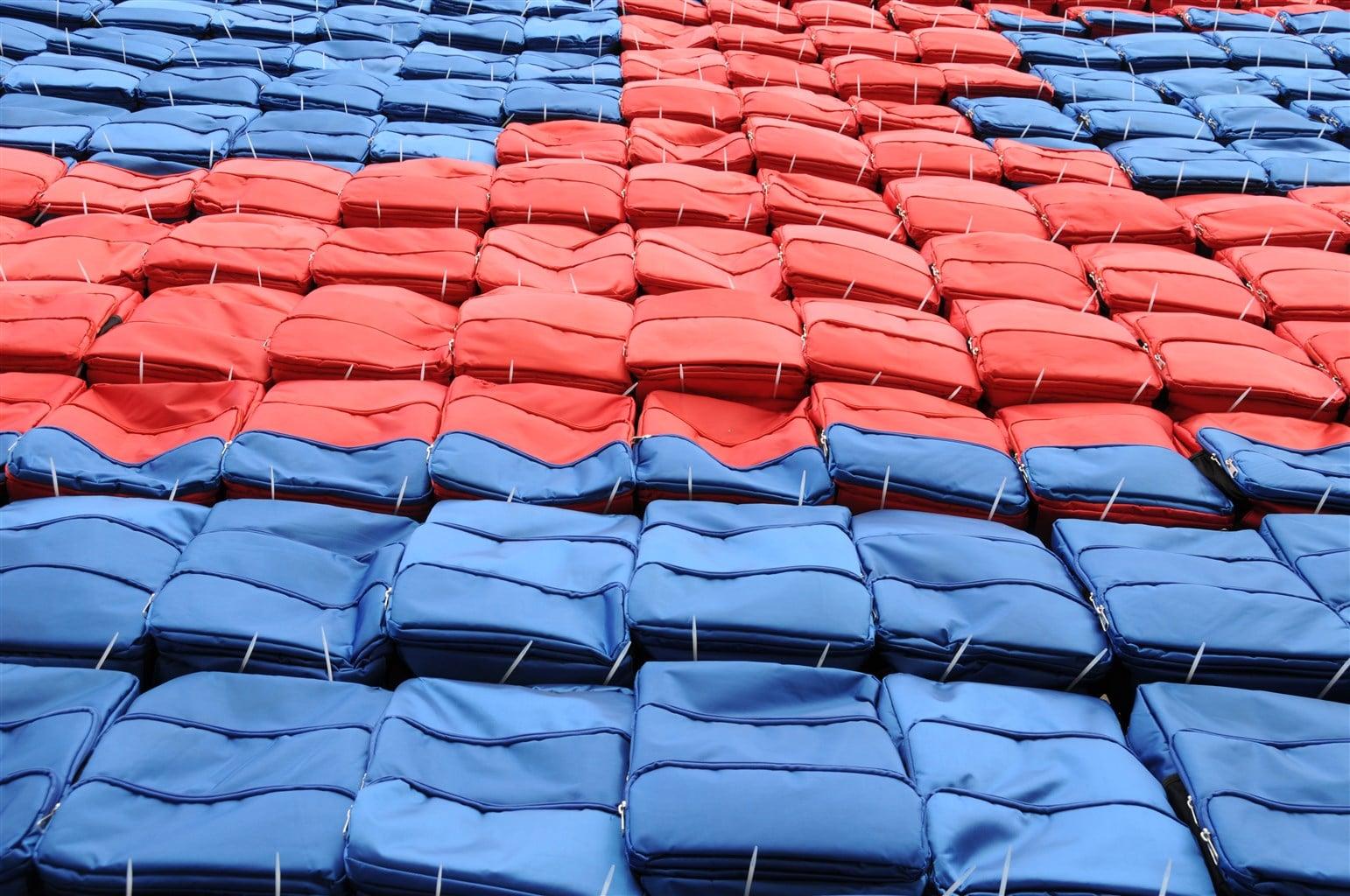 Blaue und Rote Rücksäcke in Reihen angeordnet