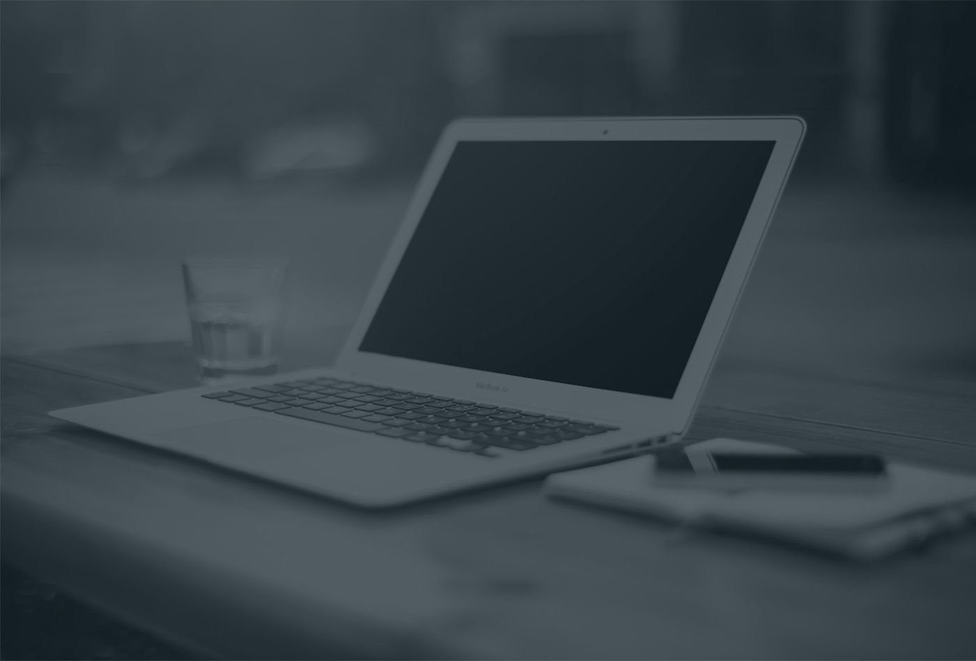 Macbook, Wasserglas und Block auf Schreibtisch - Schwarz/Weiß